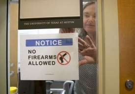 Pauline Strong posting a sign prohibiting guns in her campus office. Source: The Statesman, Jay Janner