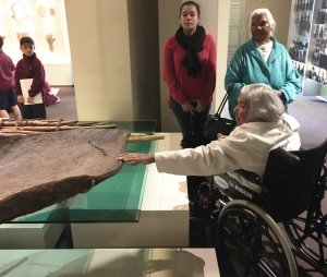 A Barkindji elder lays her hands on the canoe: 'This is what our collection is about. These women had waited their whole lives to touch it,' Carty says.  Source:  John Carty/South Australian Museum